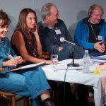 vier lachende Personen in Diskussionsrunde