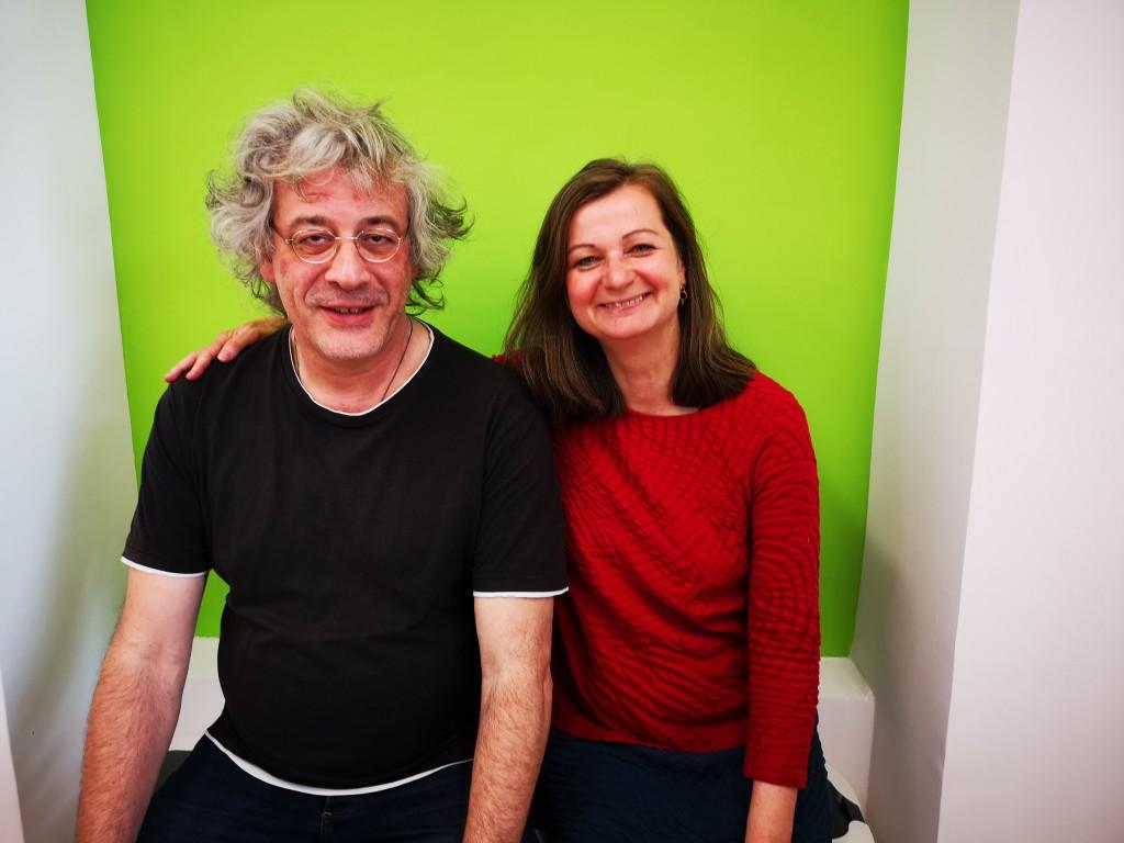 ein Mann und eine Frau sitzen und lachen in Kamera
