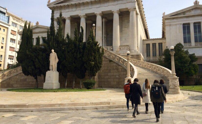 Menschengruppe vor klassizistischem Gebäude